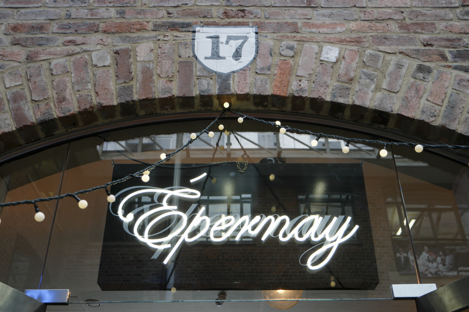 neon sign against grade 2 listed brick wall spelling epernay with the number 17 in black and white hand painted