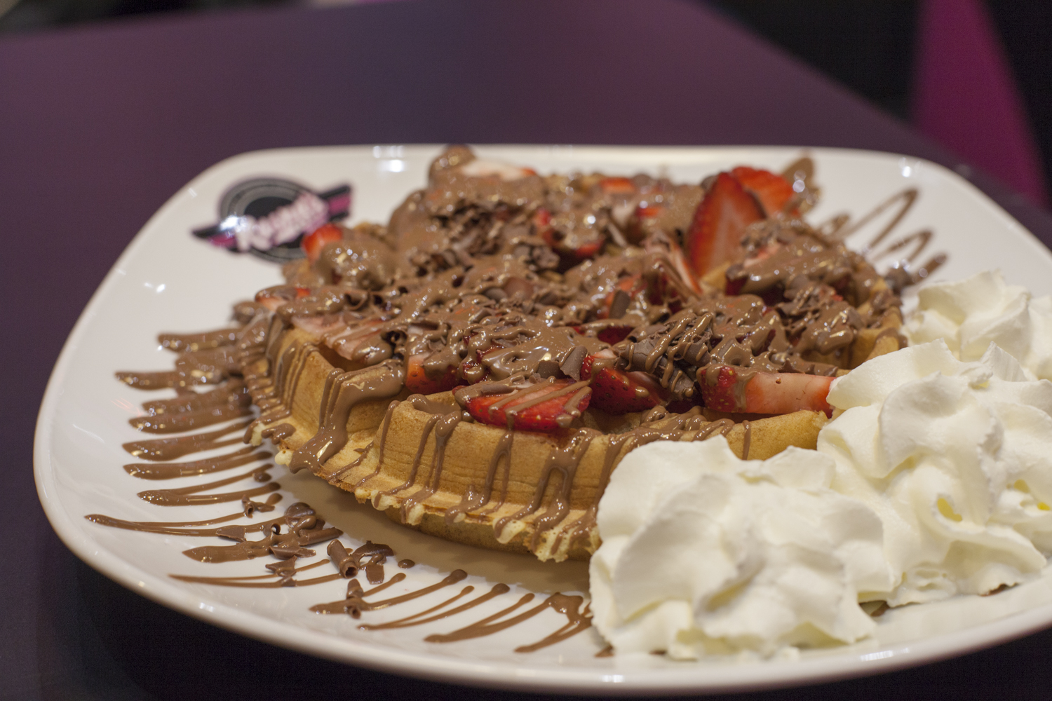 strawberry and chocolate waffle with whipped cream on a white plate in kaspas leeds