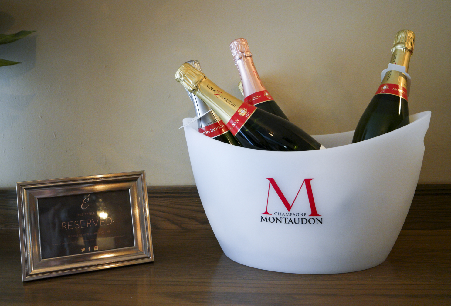 Bottles of champagne cooling in a Champagne bucket with ice on a wooden table next to a reserved sign