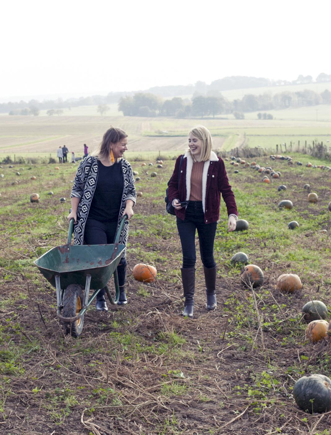 2 girls pumpkin picking with a green wheelbarrow at farmer copley in pontefract