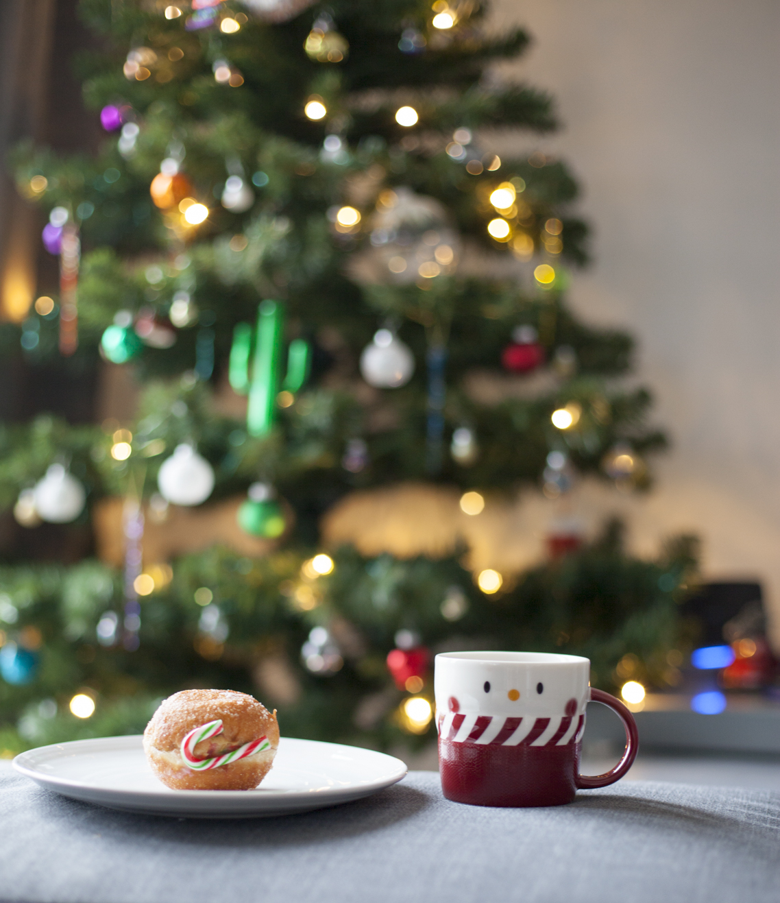 Mulled wine and a christmas doughnut donut in front of a christmas tree