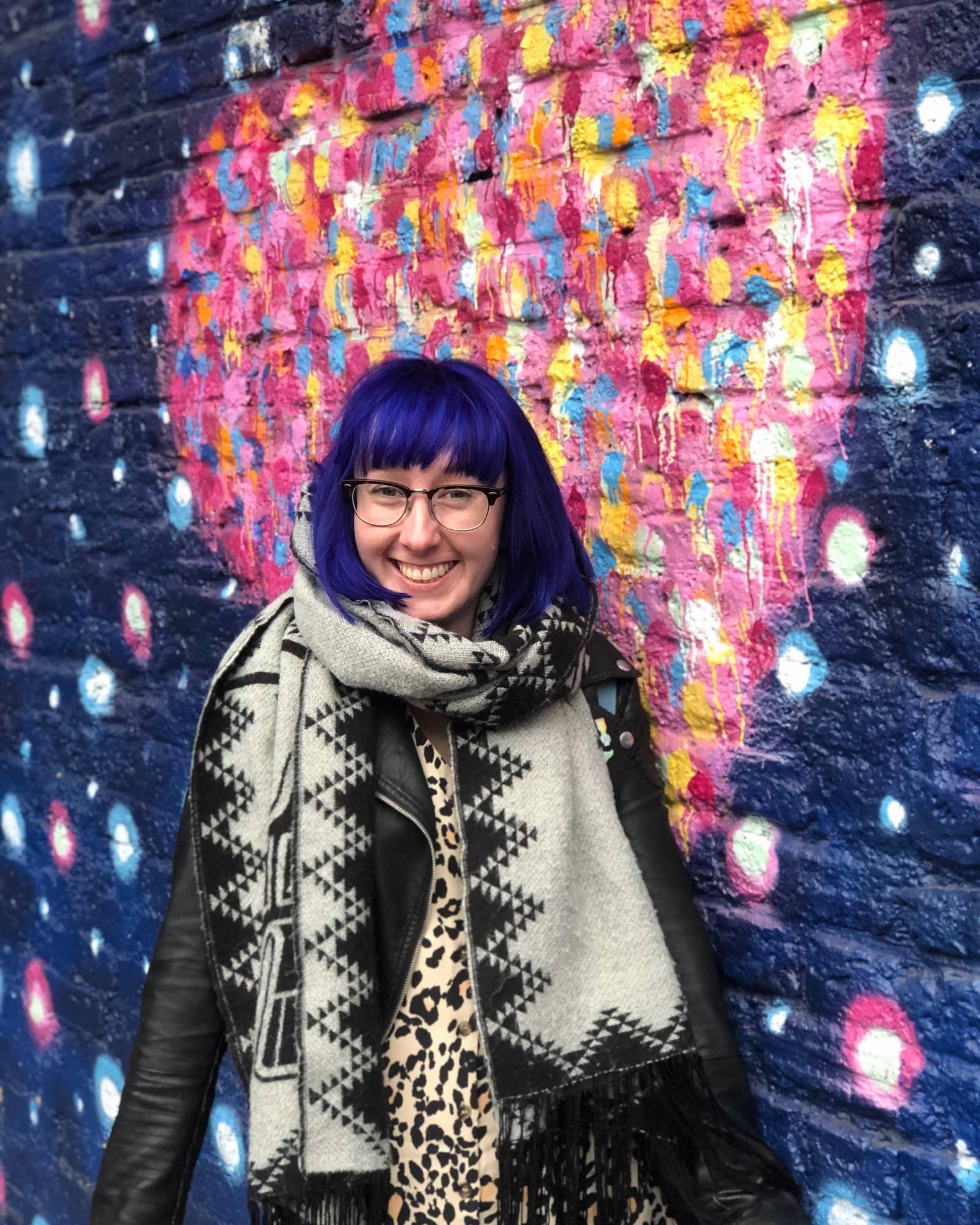blue hair in London against graffiti