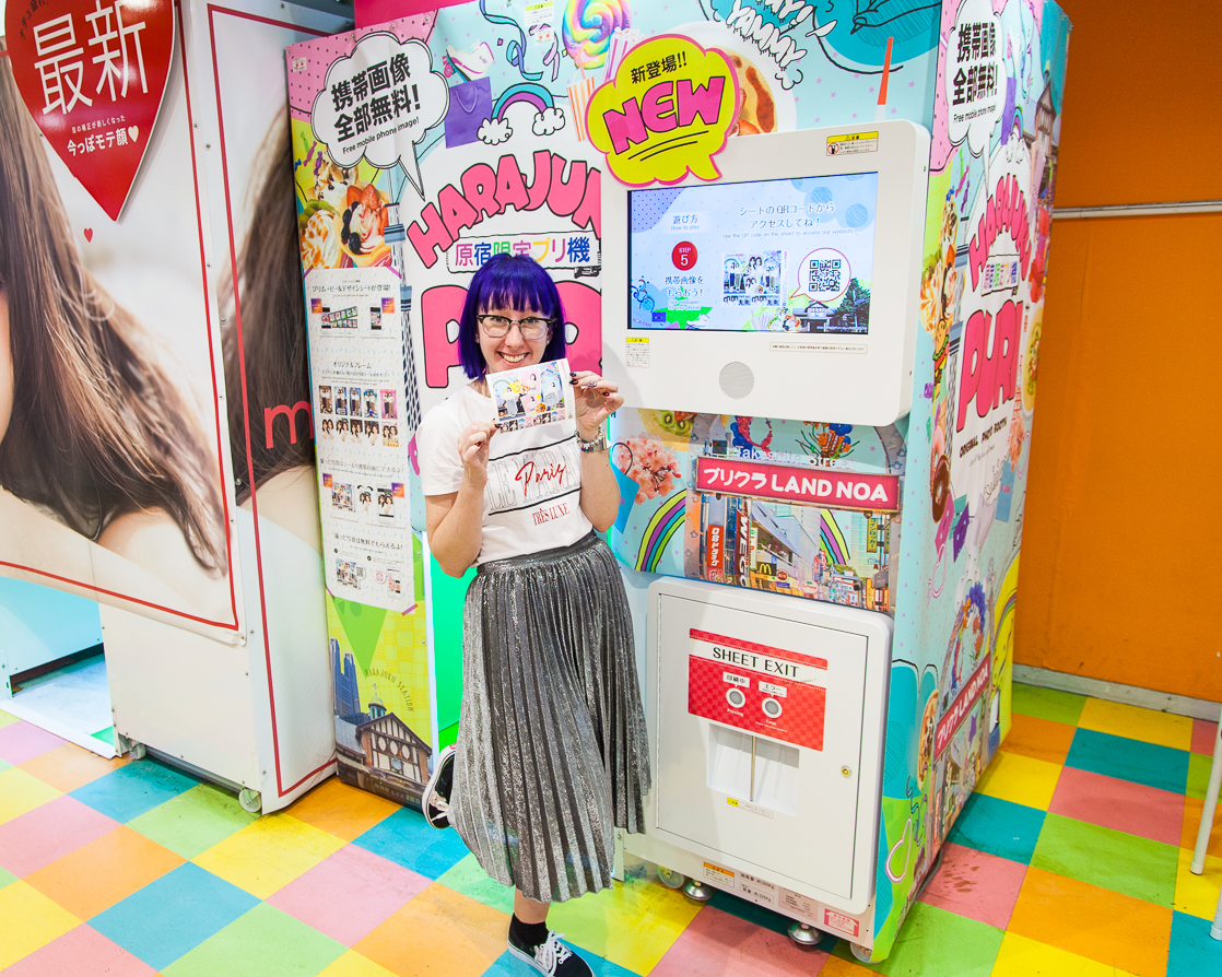 blue haired girl in from of Purikura machine holding photographs