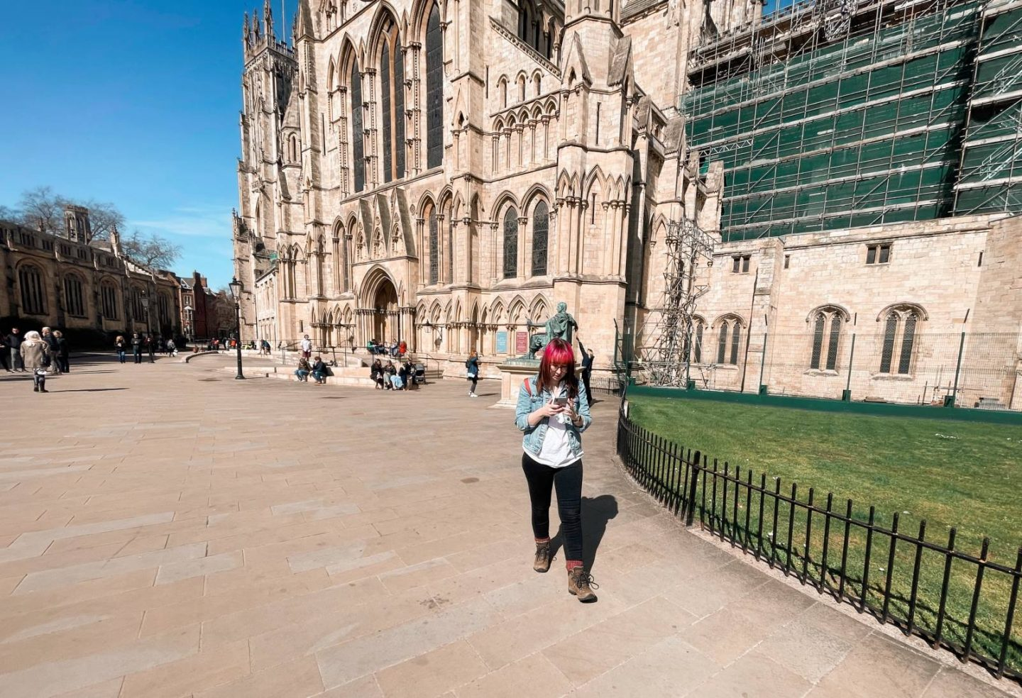 Woman with pink hair in front of York Catherdral doing a treasure hunt. Wearing black skinny jeans and walking boots