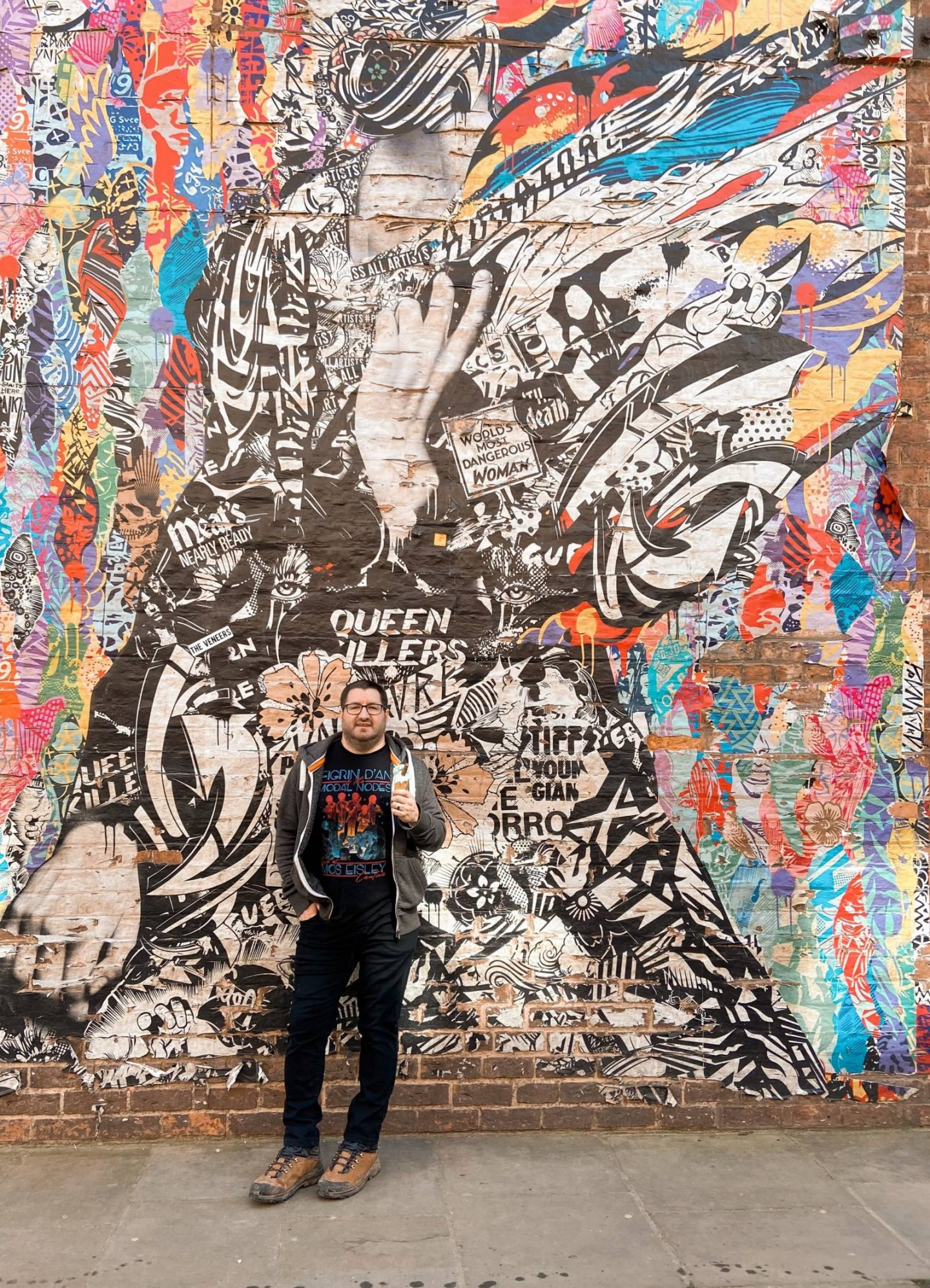 A man stood against a wall of graffiti holding a vegan ice cream in York